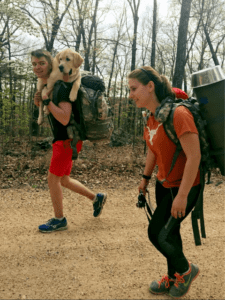 A couple hiking with their dog