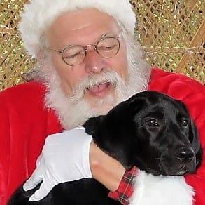 A black dog held by Santa
