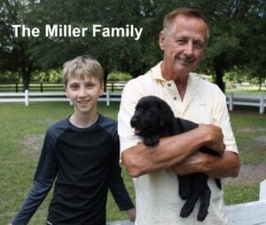 The Miller family and their black puppy