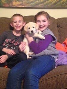 Puppy between two kids