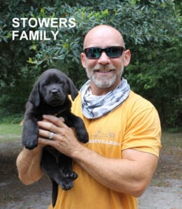 The Stowers family and a black puppy