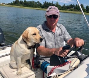 A dog next to a man driving a boat