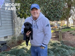 The Moore family and their black pup