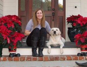 A woman and a dog sitting in front of their front door