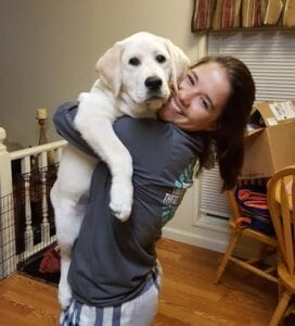 A woman carrying a big dog