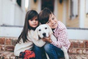 Two kids hugging a dog